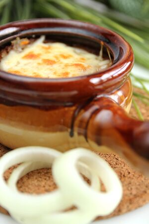 Onion soup with cheese in a bowl with fresh onion photo