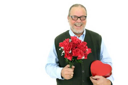 Smiling senior man holding a bouquet of red rose flowers and a red heart shape box on white background photo