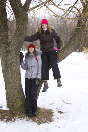 Two teenagers sit on a branch during winter season photo