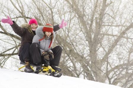 Two teenagers sliding on snow during winter season photo