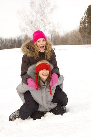 Two teenagers best friends having fun in snow photo