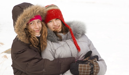 Two teenagers best friends with hats and winter coat smiling  photo