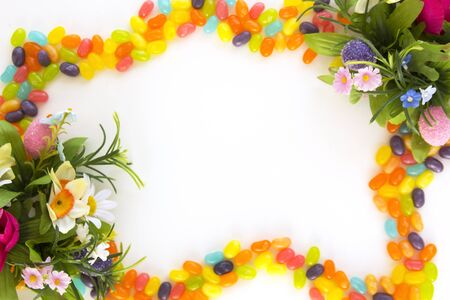 Sweet and colorful jelly beans frame with easter flowers Stock Photo