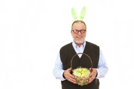 Senior man with green rabbit ears holding a easter basket full of yellow eggs photo