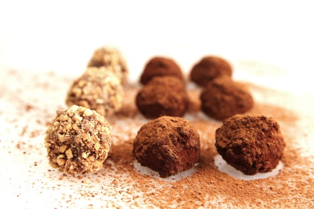 cocoa powder: nine chocolate truffles with cacao powder on white background Stock Photo