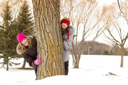 Two teenagers hide behind a huge tree during winter season photo