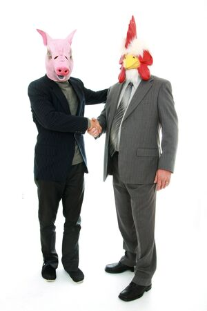 Two business man with animals mask, pig and chicken shaking hands on a white background Stock Photo - 8969046