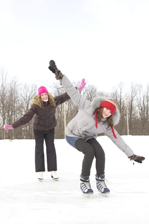 Two girl friends doing plane with arms and skating on a lake