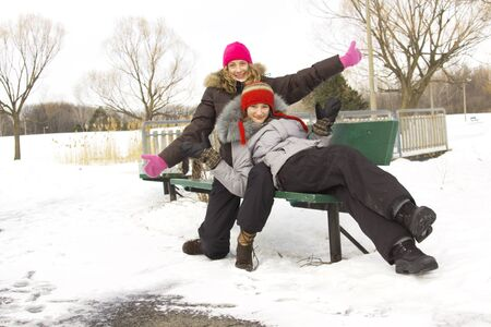 Two teenagers best friends sit on a bench during winter season photo
