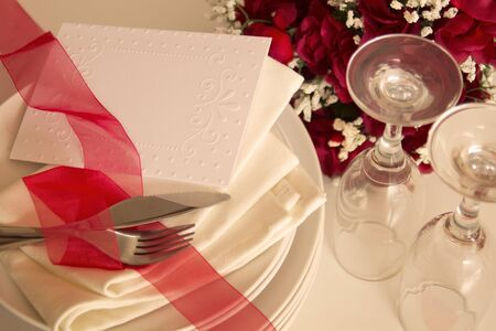Table setting with red roses, glass on white and invitation