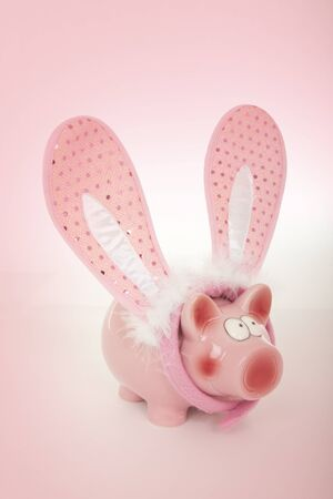 pink rabbit: Pink piggy bank with pink rabbit ears for easter Stock Photo