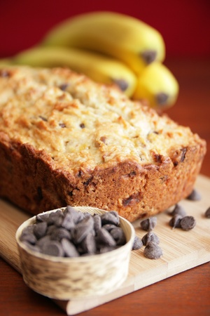 Banana bread with chocolat chip it and banana in background
