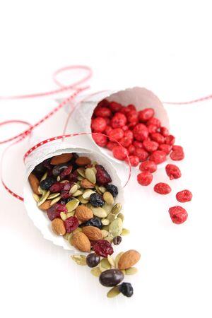 Twee papier met verscheidenheid van noten, droge vruchten en chocolade op wit Stockfoto