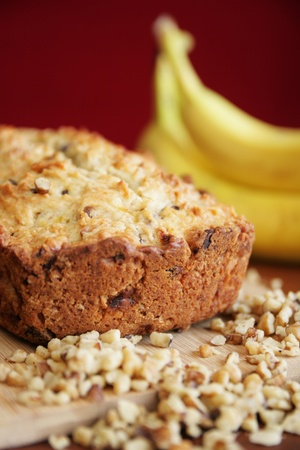 Warm banana bread on a cutting board with fresh banana in background and nuts