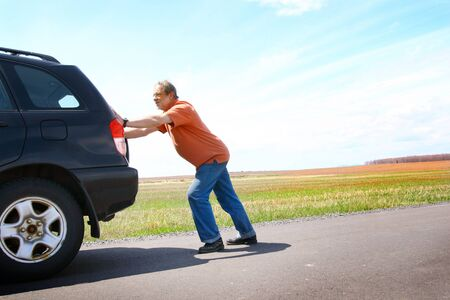 troubles: Senior man pushing his broken car Stock Photo