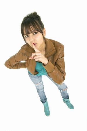 secret teenaer with her finger on lips having a secret Фото со стока