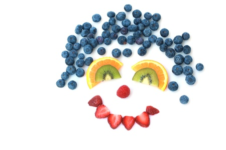Happy face made with fresh fruits.  Strawberry, blueberry, raspberry, kiwi and orange.