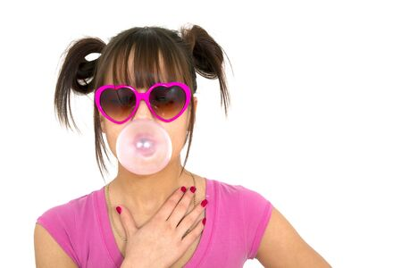 Teenager wearing heart shape glasses blowing a big bubble with chewing gum on white background