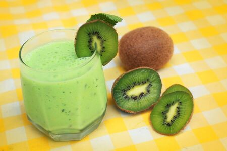 Green smoothie and fresh kiwi on yellow tableclothes Banco de Imagens