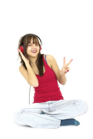 young teenager listening music with red headphone and doing a peace sign photo