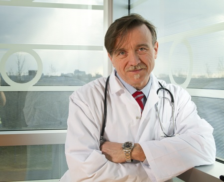 Mature doctor with crossed arms looking at the camera photo