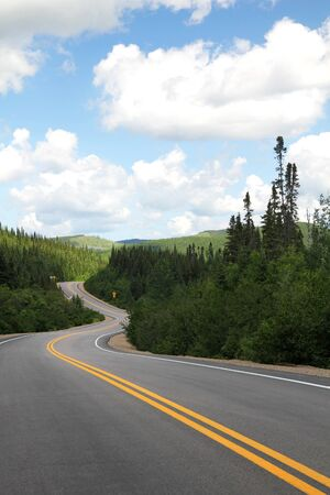 Winding road into the canadian green mountains photo