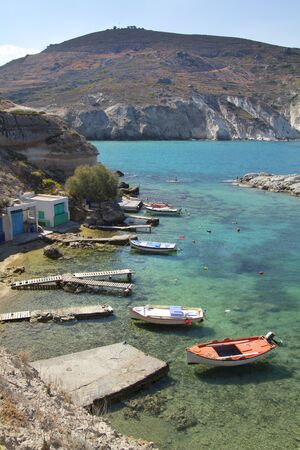 Little boats with their shed on a turquoise water at Milos island, Greece photo