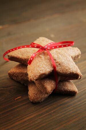 Star cookies with red ribbon on a wooden table photo