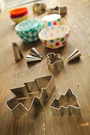 wood cutter: Muffin papers, cookies cutter and decorating nozzles on a wooden table Stock Photo