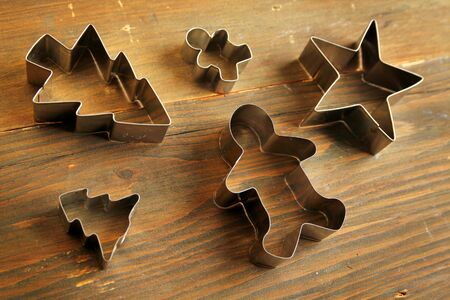 wood cutter: Five cookie cutter on a wooden table
