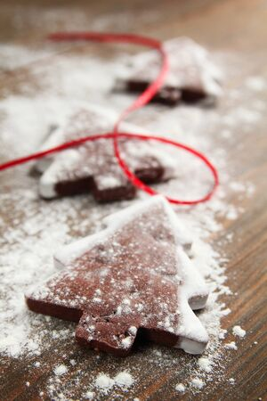 Christmas tree cookies with powder sugar and red ribbon on a wooden table photo