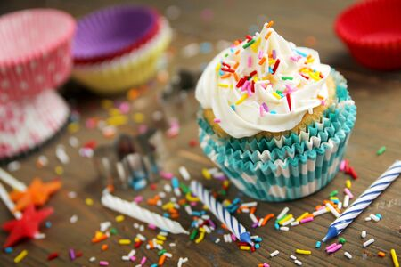 Vanilla cupcake with candles, paper and candies on a wooden table photo