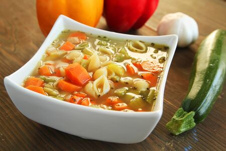 Vegetables soup with fresh vegetables on a wooden table Banco de Imagens