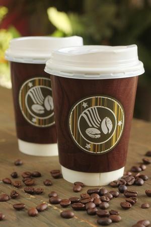 Dos taza de café para llevar en una mesa con granos de café