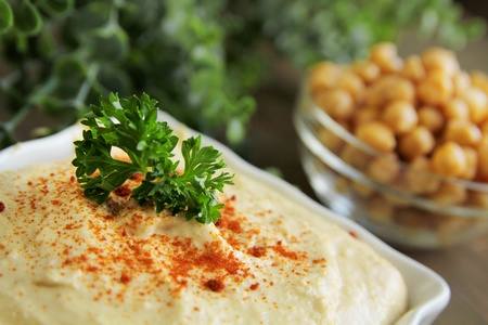 Close up of hummus with chickpeas on a wooden table