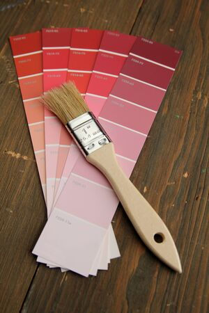 Brush with wood handle on a red color palette photo