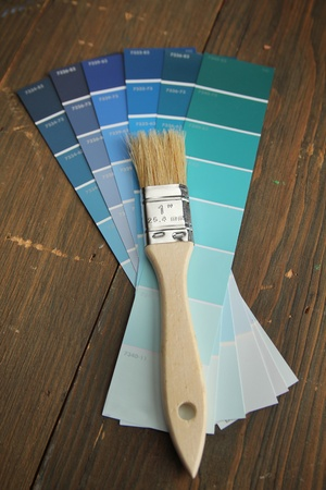 Brush with wood handle on a blue color palette photo