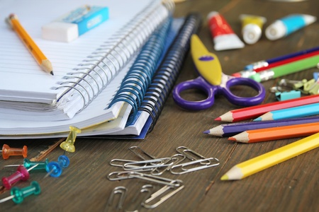 school desk: Material for school, paper clips, pencils, colors, cisor and notebook Stock Photo