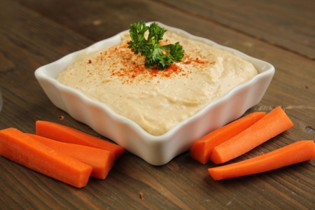 Hummus in a white container with fresh carrots