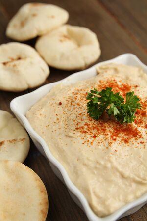 Hummus in a white container with mini pita bread