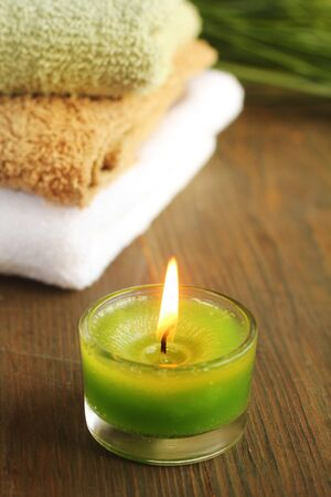 Green candles with towels in a background