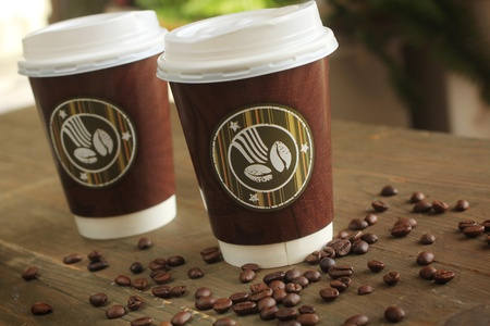 Two paper cup of coffee to go on a table with coffee beans