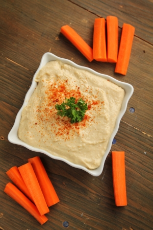 Top view of a hummus in a white container with fresh carrots Stock Photo