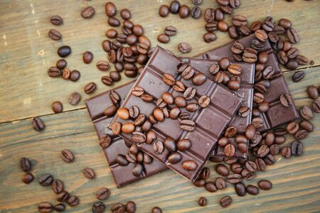 Dark chocolate and coffee beans on a wooden table