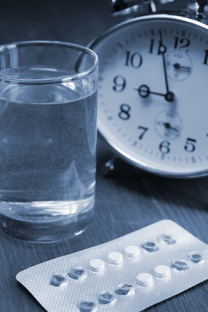bedside table: Birth control pills and a glass of water on a bedside table