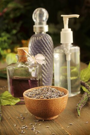 Lavender items, oil, cream, and dried lavender in background photo