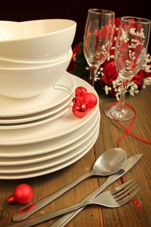 crockery: Plain white plates, bowls and glass of wine with cutlery and christmas red balls Stock Photo