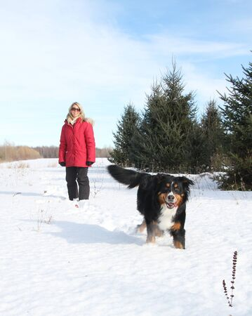 Woman with red jacket and dog during winter photo