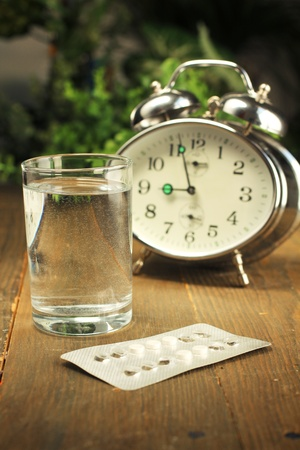 bedside: Las p�ldoras anticonceptivas y un vaso de agua sobre una mesita de noche Foto de archivo