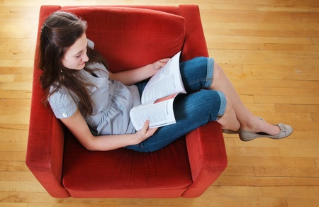 sit: Teen sit in a sofa and read a magazine